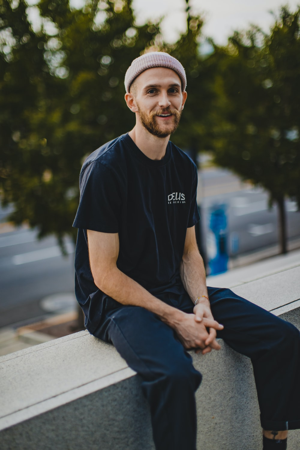 man in black crew neck t-shirt and blue denim jeans sitting on gray concrete bench