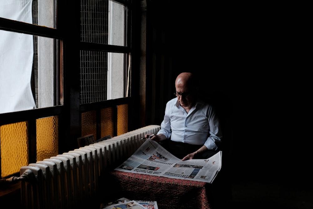 man in white dress shirt reading newspaper