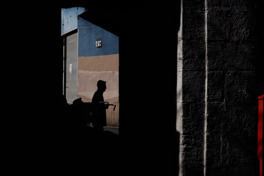 man in black shirt sitting on chair near blue door