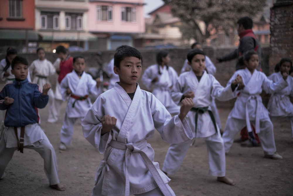 boy in white robe holding a stick