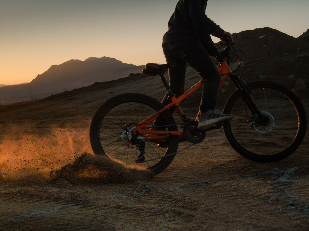 man in black jacket riding on red and black mountain bike on brown field during daytime