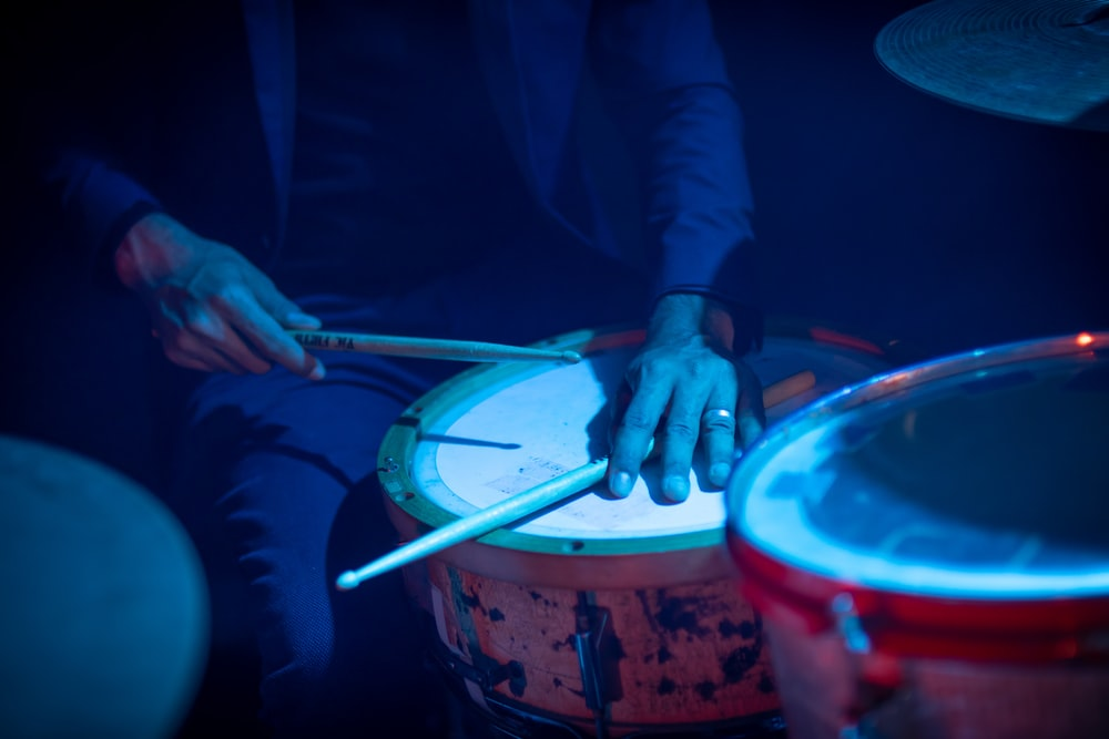 person in blue long sleeve shirt holding drum sticks