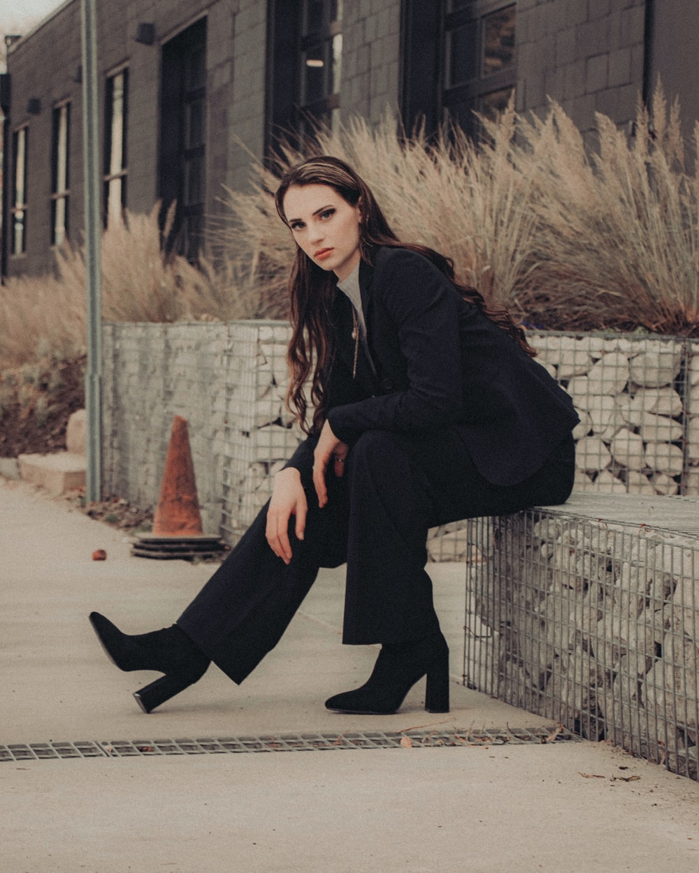 woman in black coat and black pants sitting on concrete wall during daytime