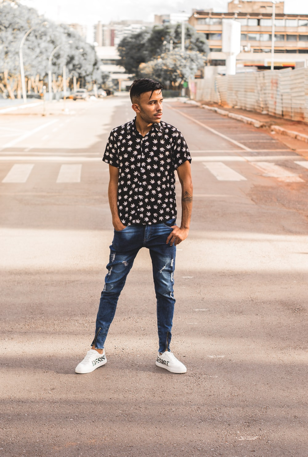 man in black and white polka dot shirt and blue denim jeans standing on road during