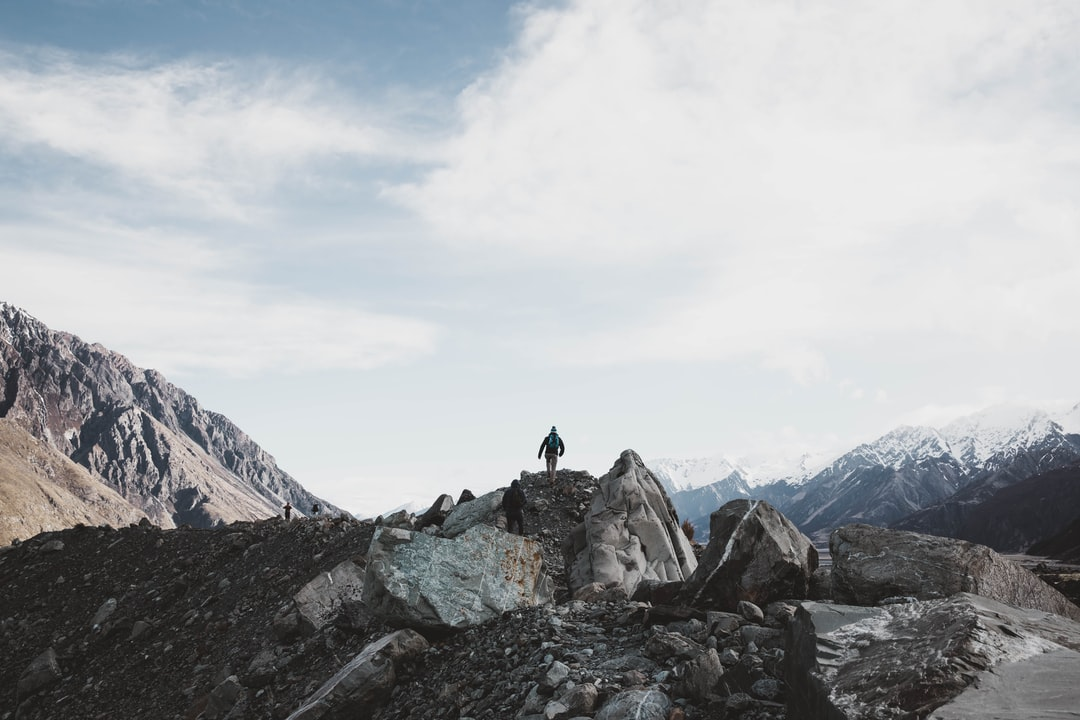 Person Standing On Rocky Mountain During Daytime - unsplash