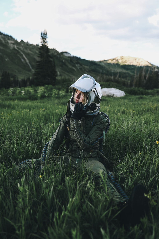 man in black jacket wearing white helmet sitting on green grass field during daytime