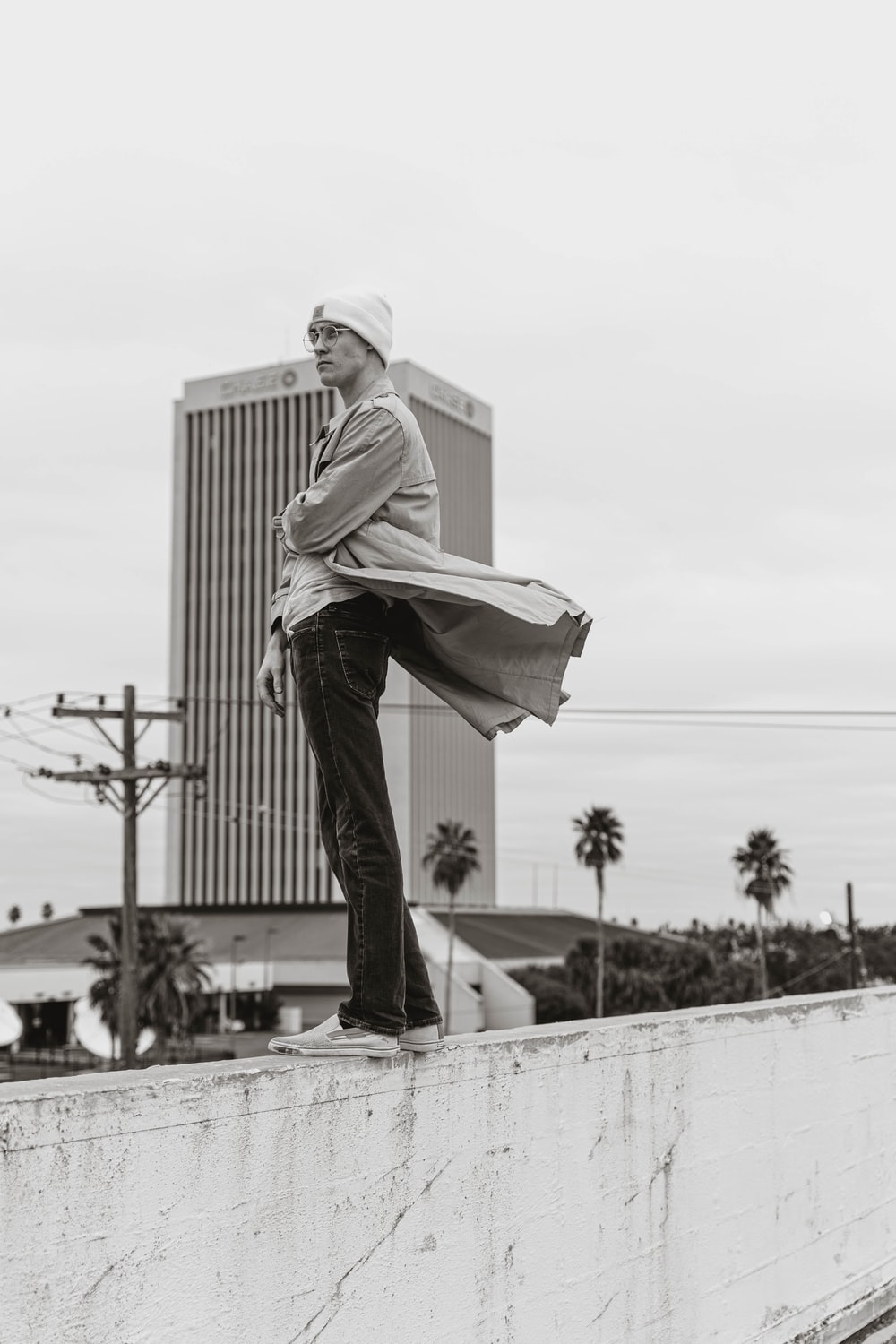 man in white long sleeve shirt and black pants standing on white concrete wall during daytime
