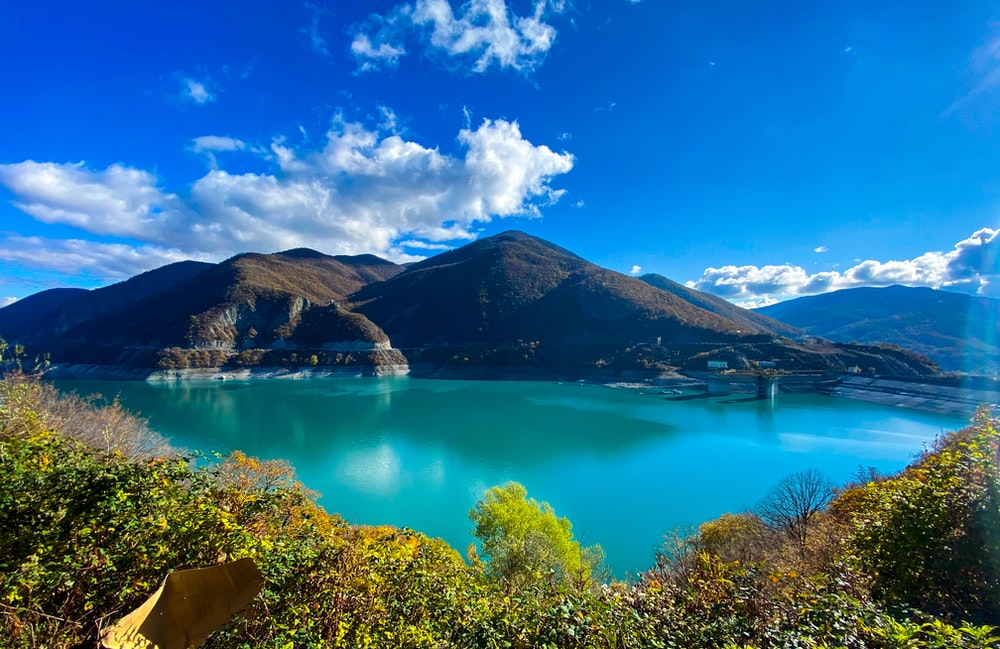 lake surrounded by green trees and mountains under blue sky during daytime