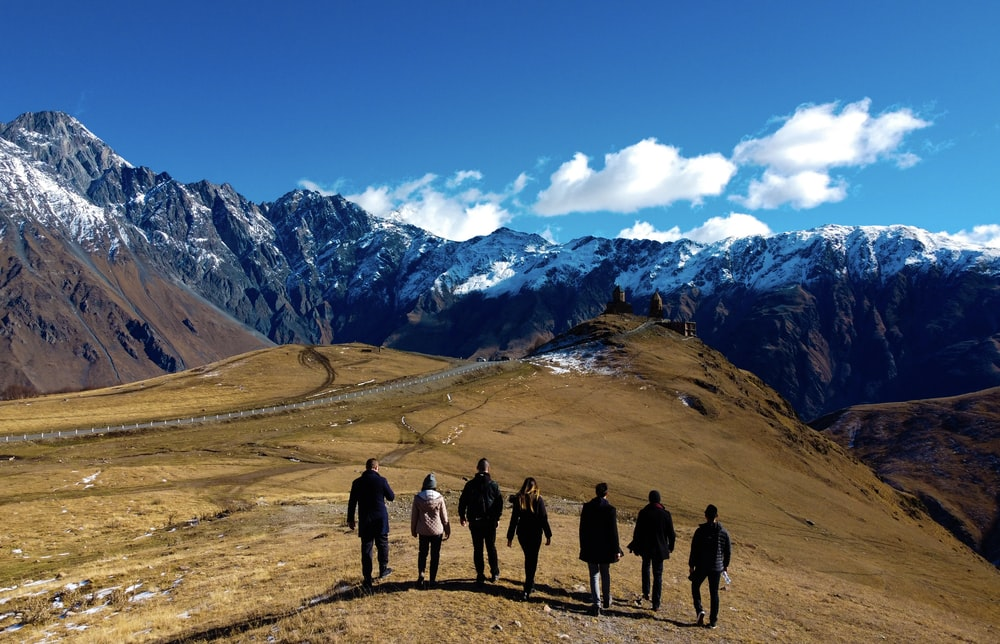 group of people standing on brown field near snow covered mountain during daytime