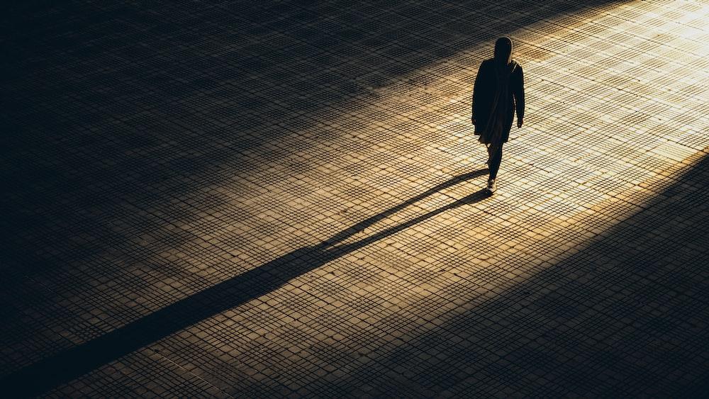 man in black jacket walking on brown brick floor