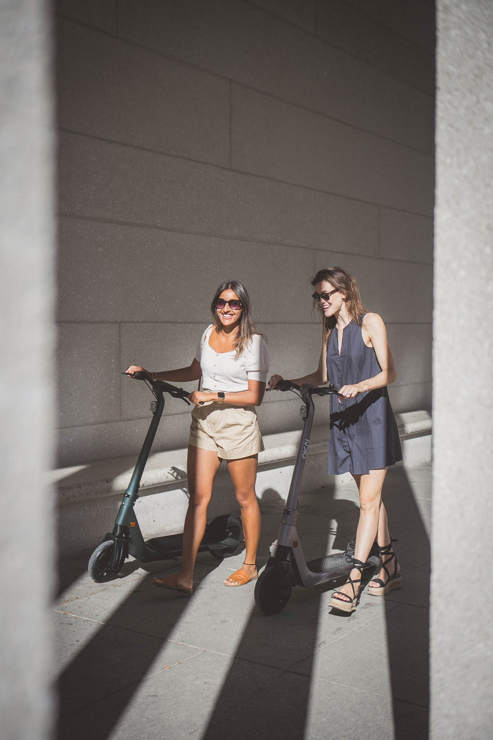 2 women are laughing when riding with electric scooters