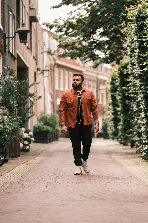 man in orange jacket and black pants standing on sidewalk during daytime