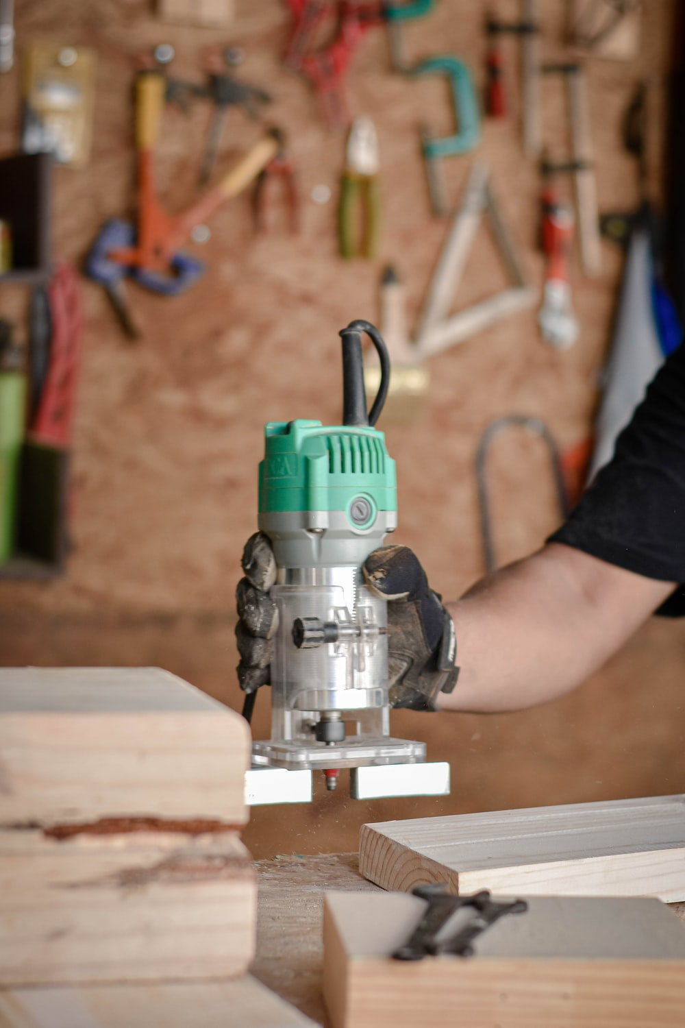 person holding green and gray power tool