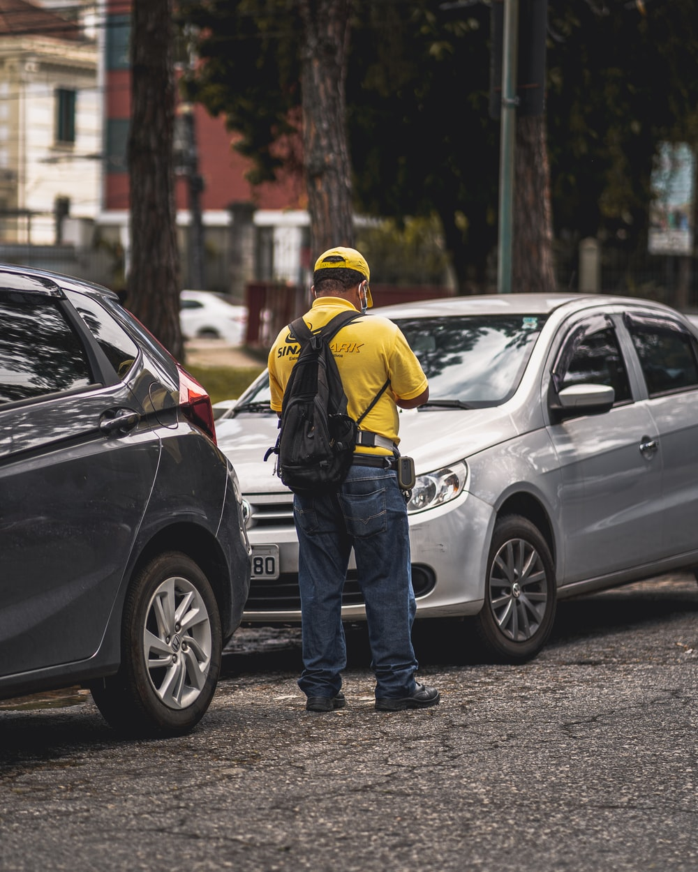 man in yellow hard hat standing beside black suv during daytime