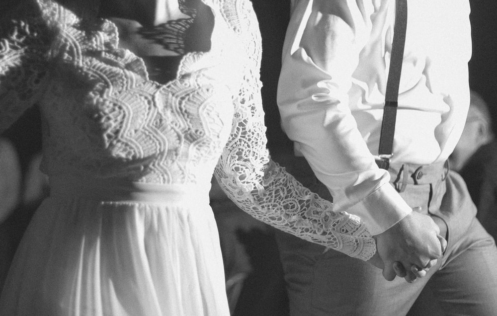 man in white dress shirt and woman in black and white floral dress