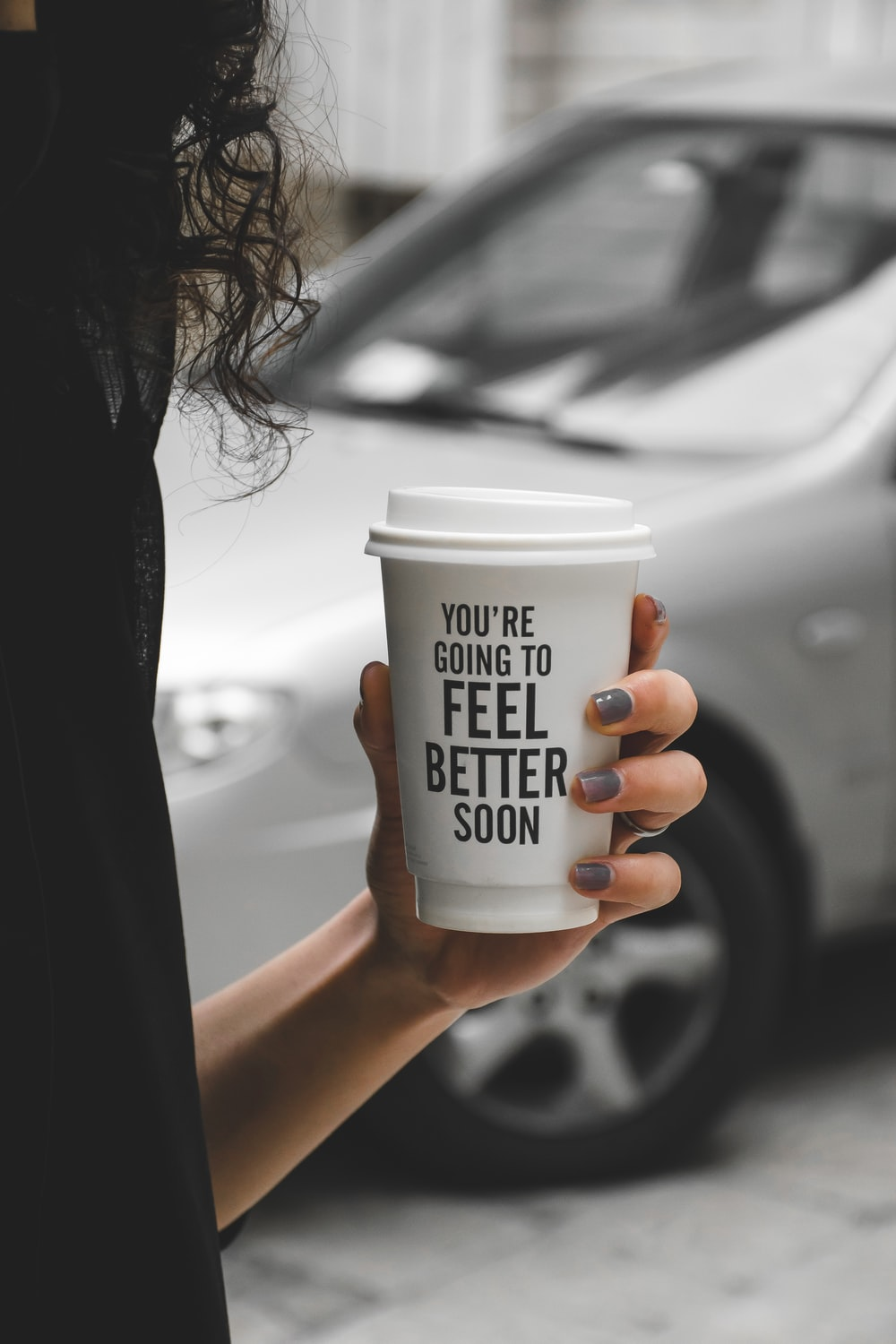 woman holding white and black disposable cup