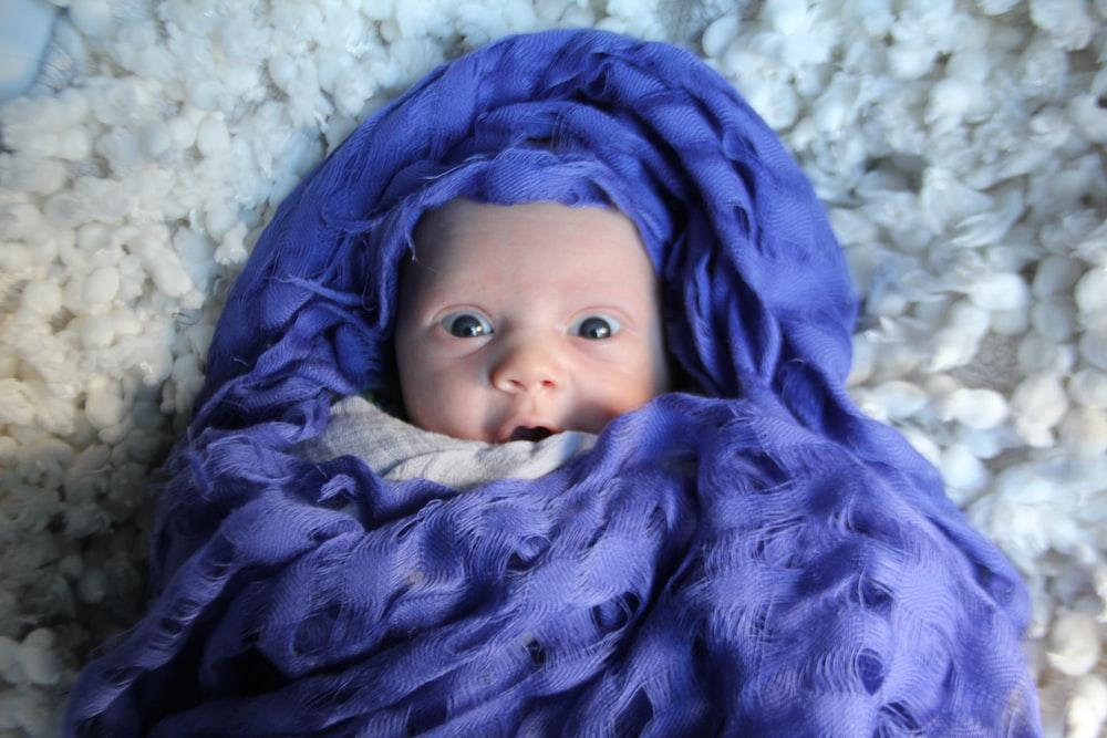 baby lying on blue blanket