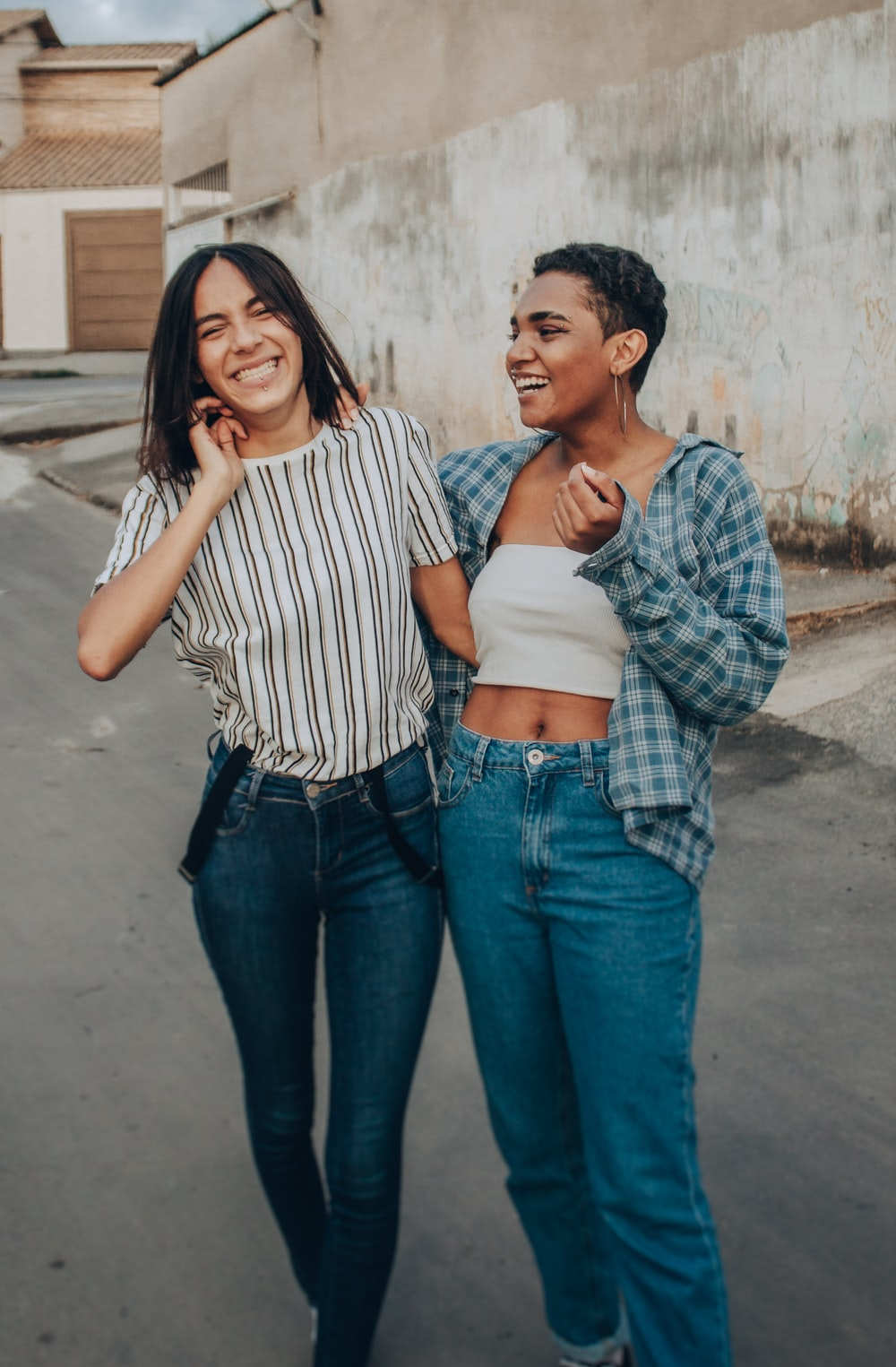 woman in white and black striped shirt and blue denim jeans standing beside woman in blue