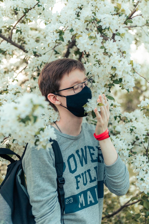 boy in gray crew neck t-shirt holding white flower