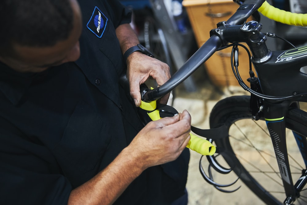 man in black polo shirt holding black bicycle handle bar