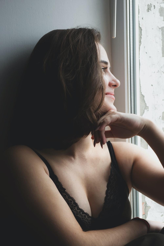 woman in black brassiere sitting on black sofa