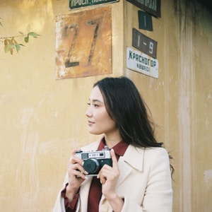 woman in white coat holding gray camera