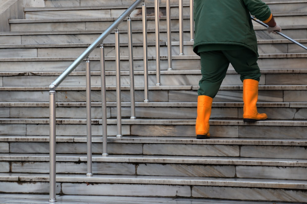 person in green jacket and brown pants walking on gray concrete stairs