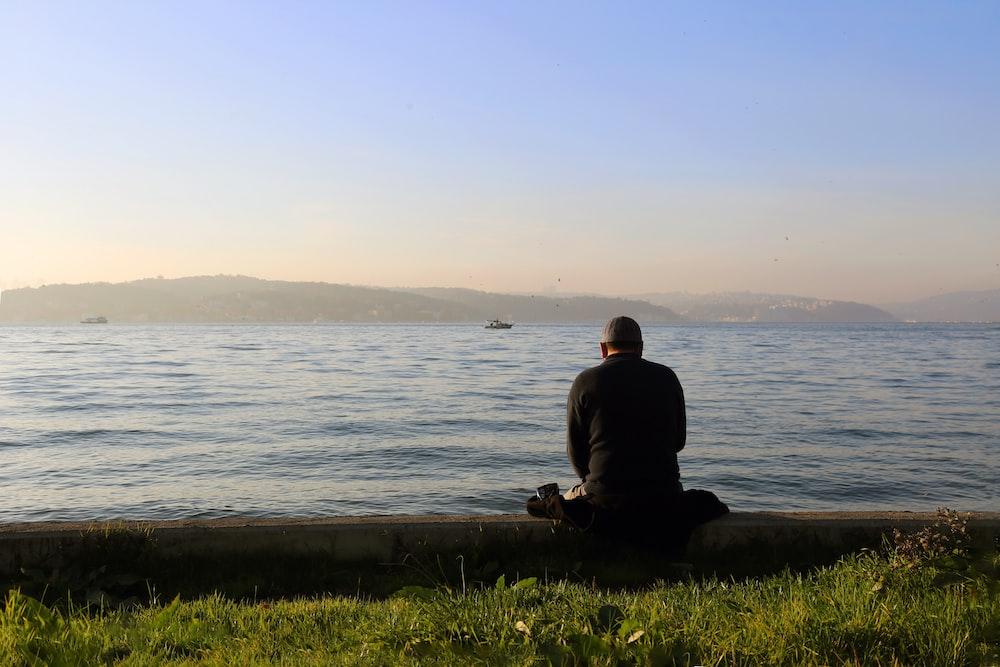 man in black jacket sitting on brown rock near body of water during daytime