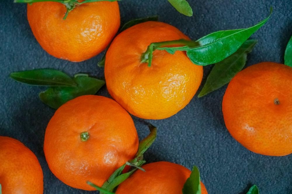 orange fruits on gray textile