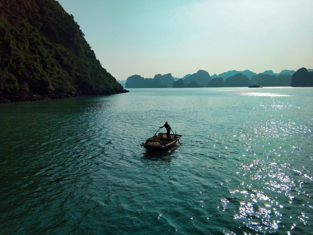 person riding on boat on body of water during daytime