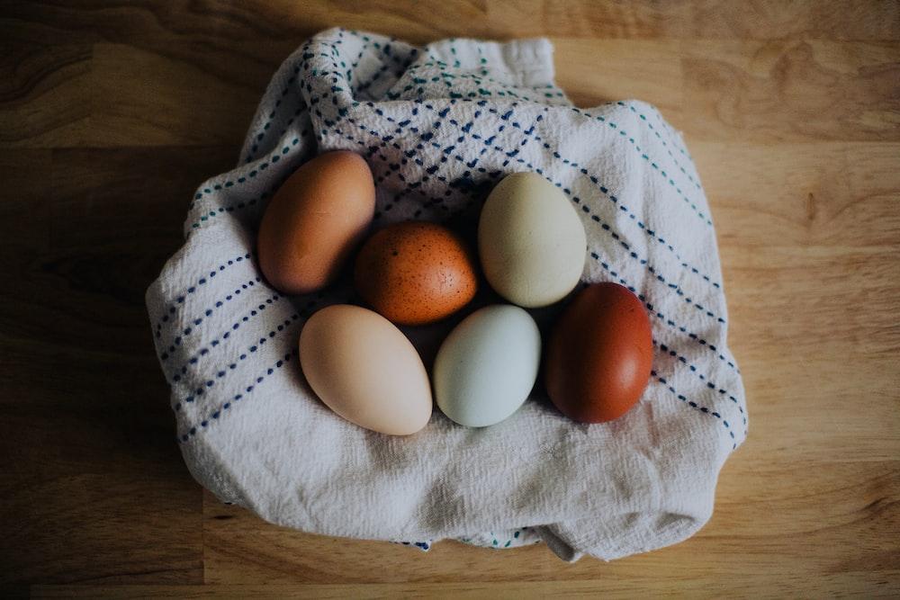 brown egg on white textile