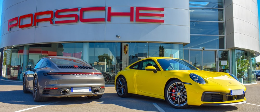 yellow porsche 911 parked in front of white and red building