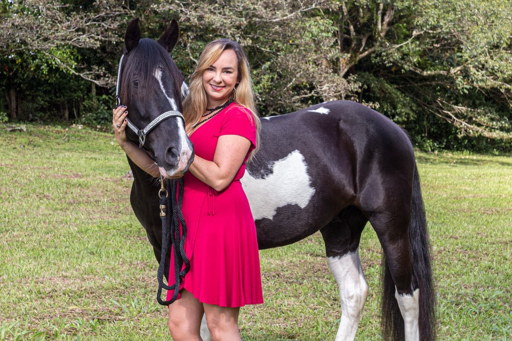 girl in red dress standing beside black and white horse during daytime