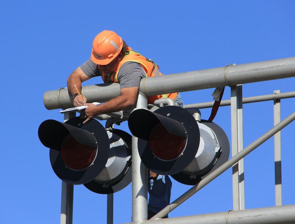 man in orange helmet climbing on white metal bar during daytime