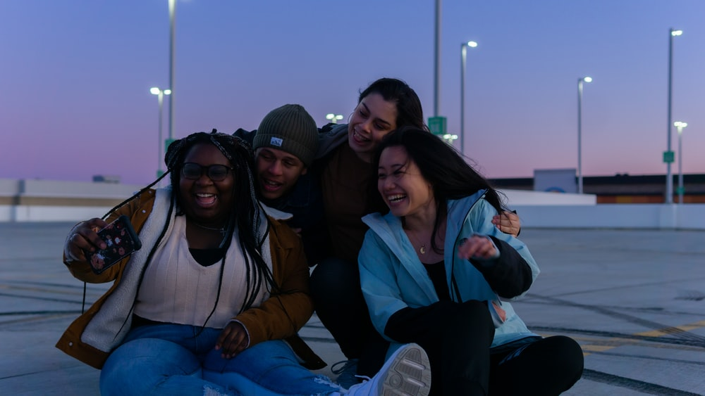 3 women and 2 men sitting on boat during daytime
