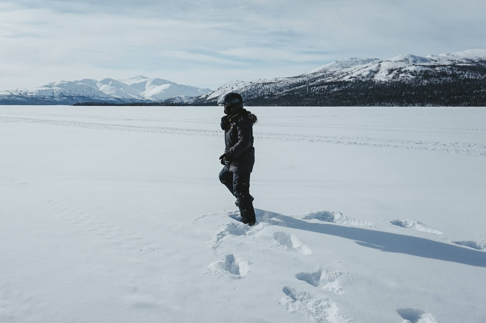 person in black jacket and black pants standing on snow covered ground during daytime