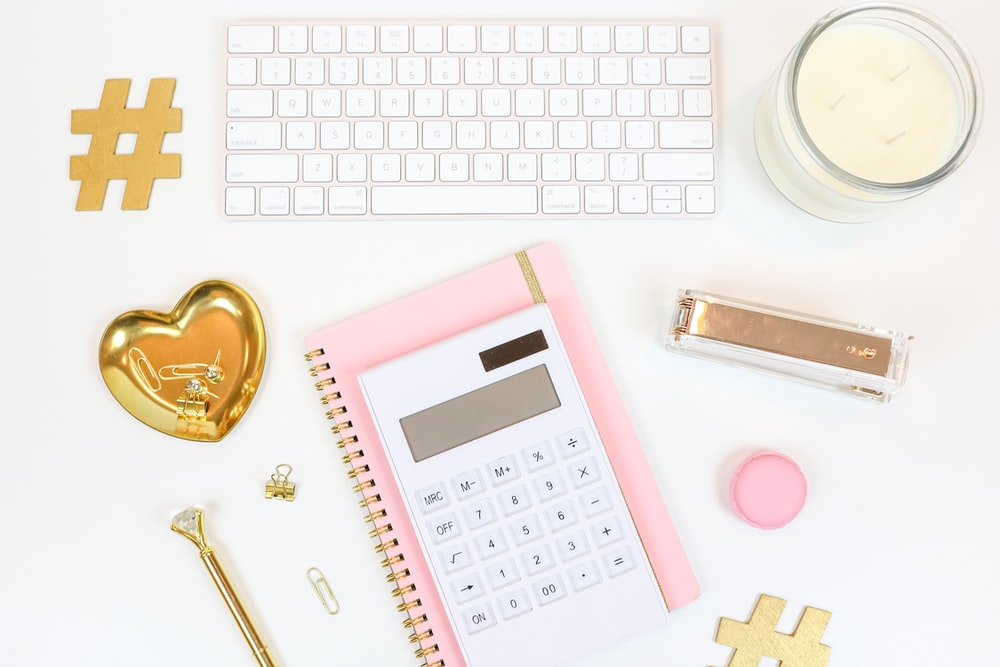 pink and white calculator beside silver and gold key