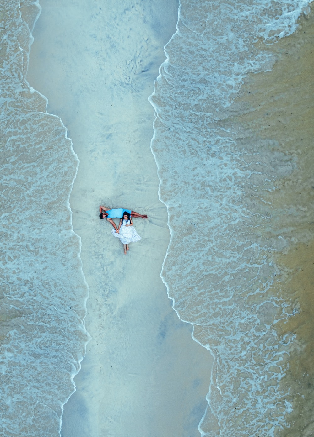2 people surfing on sea waves during daytime