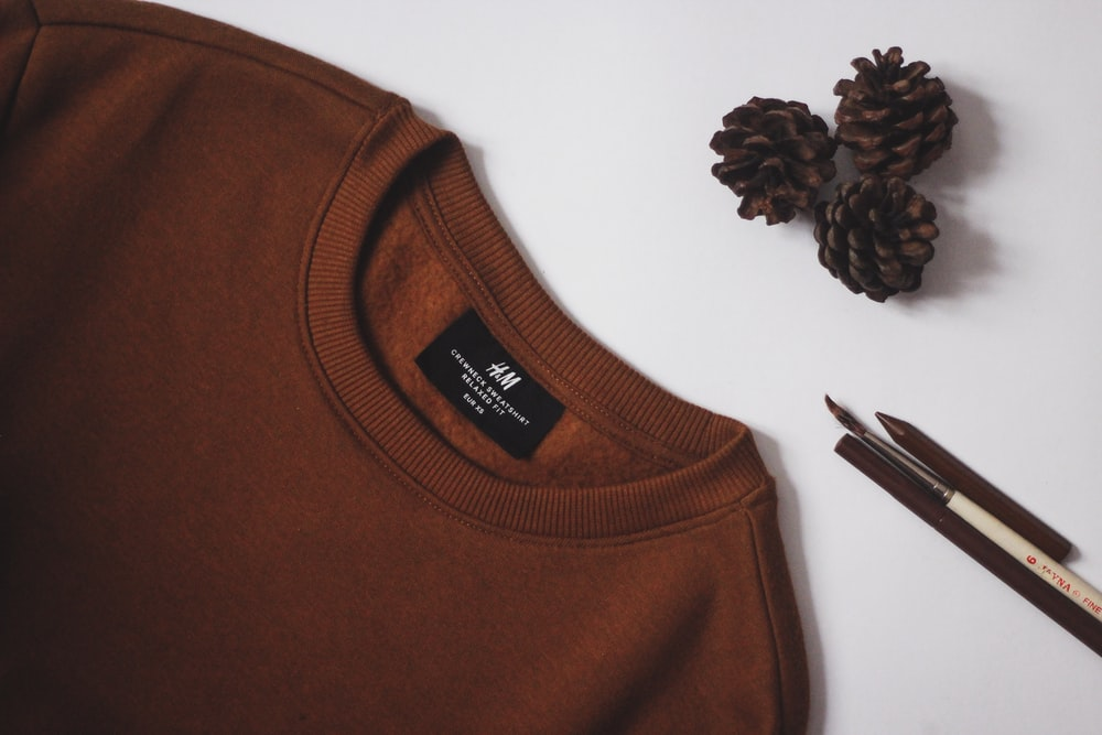 brown crew neck shirt on white table