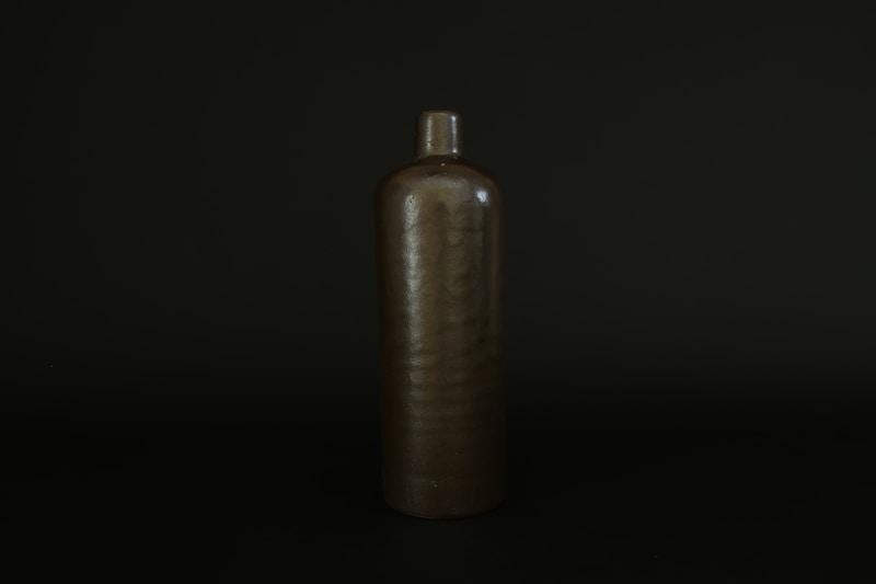 brown bottle on black surface
