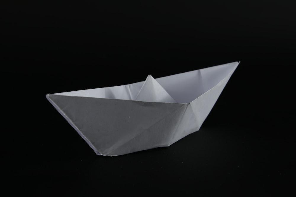 white paper boat on black background