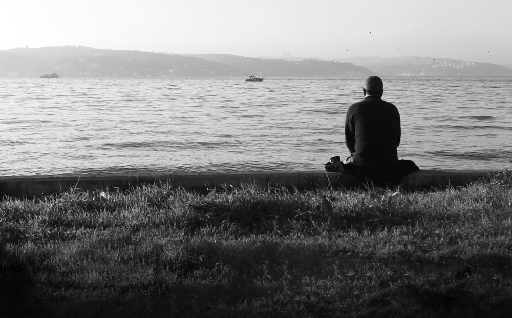 man sitting on grass near body of water