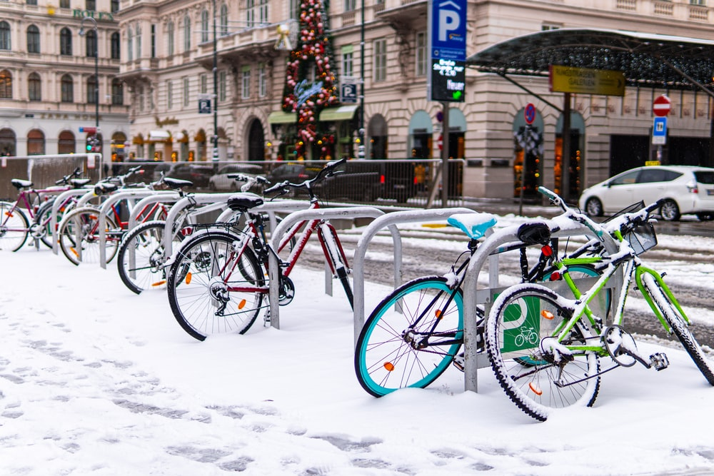 blue and green bicycles on snow covered ground during daytime
