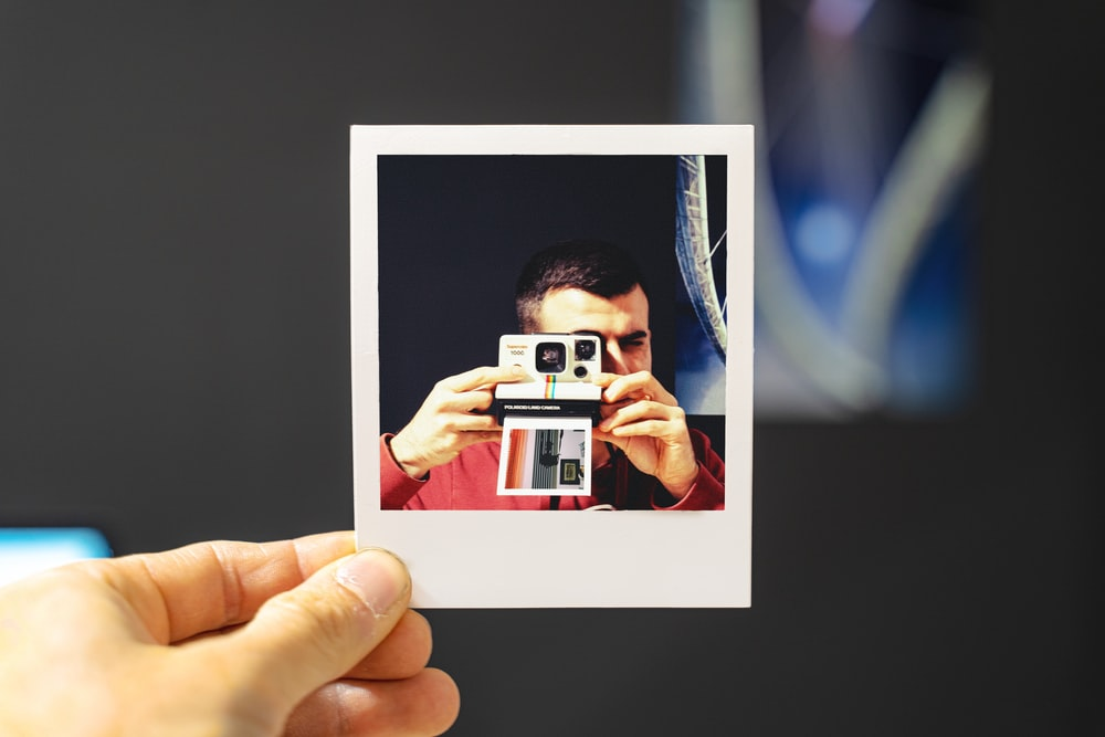 person holding white and red camera
