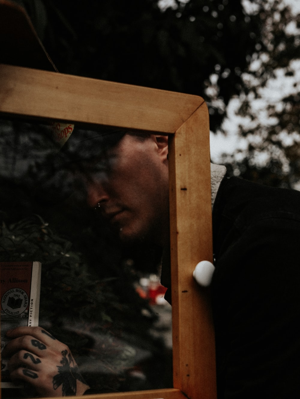 man holding a camera in a brown wooden frame