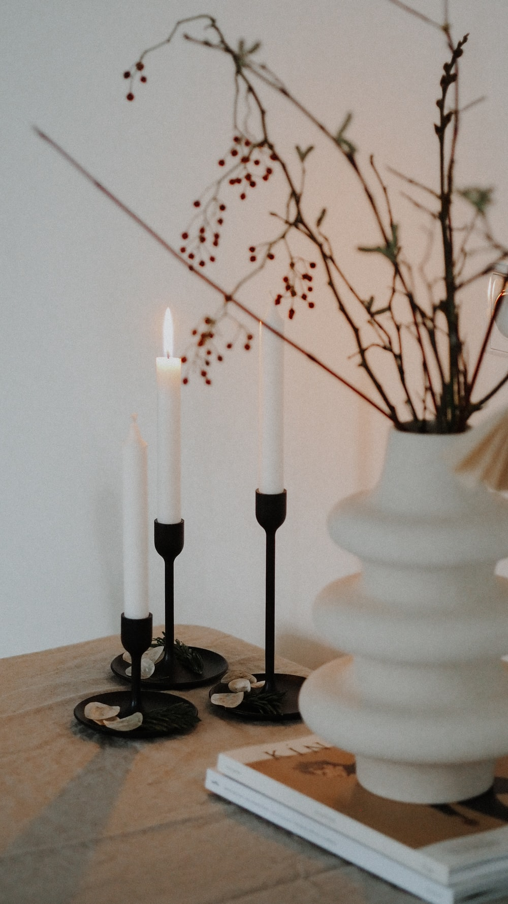 white candles on black metal candle holder