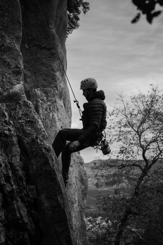 grayscale photo of man climbing on rock
