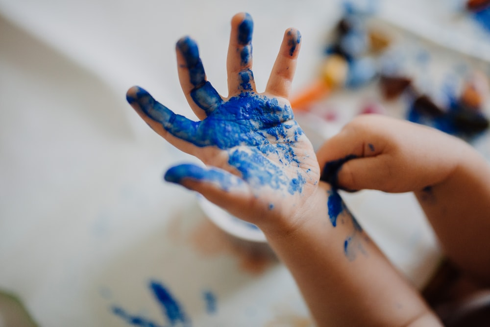 person with blue paint on hand
