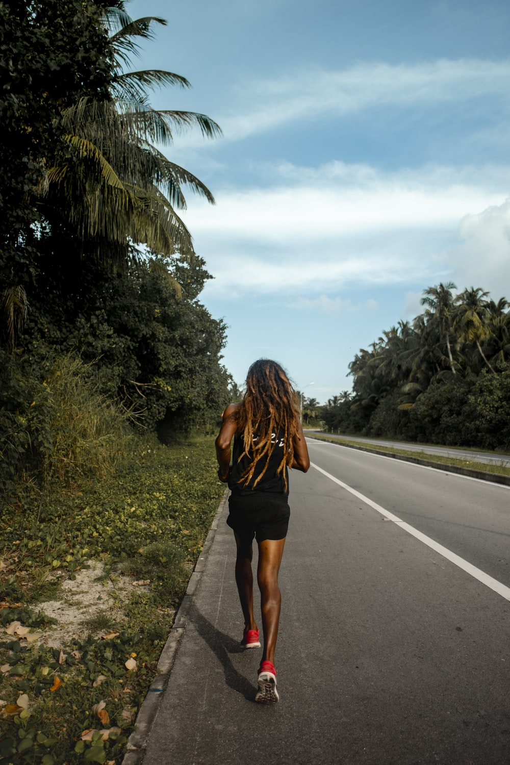 woman in black dress walking on the road during daytime