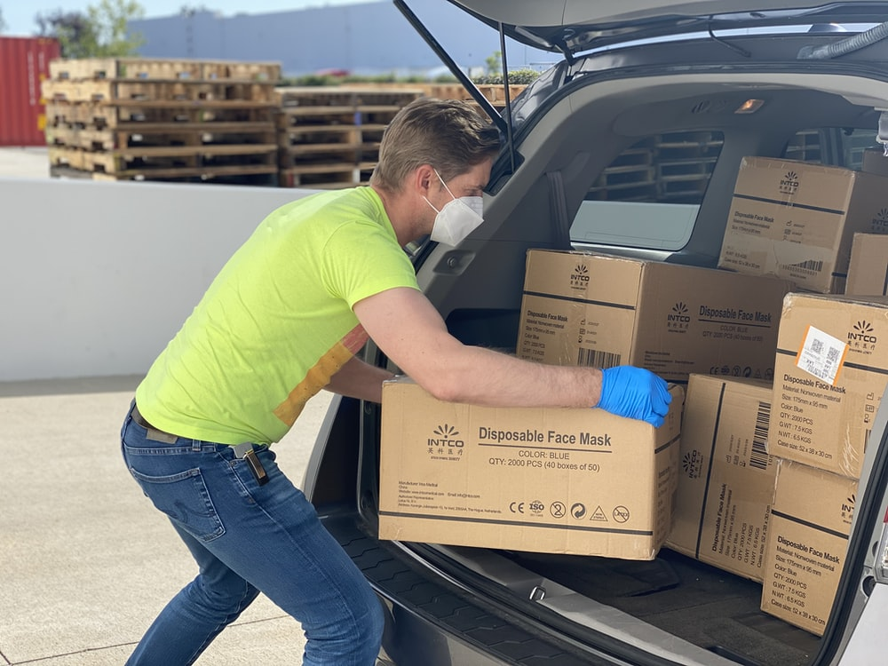 man in green t-shirt and blue denim jeans holding brown cardboard box